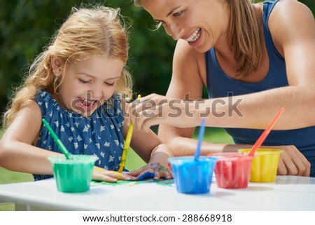 Mother and daughter painting with hands outdoors showing emotional connection - stock photo