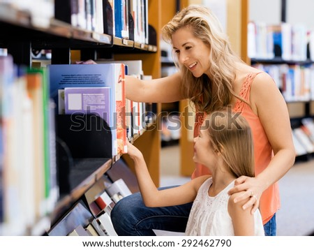 Mother and daughter picking a book in public library - stock photo