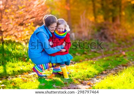 Mother and daughter play in autumn park. Parent and child walk in the forest on a sunny fall day. Children playing outdoors with yellow maple leaf. Toddler girl picking golden leaves. Mom hugging kid. - stock photo