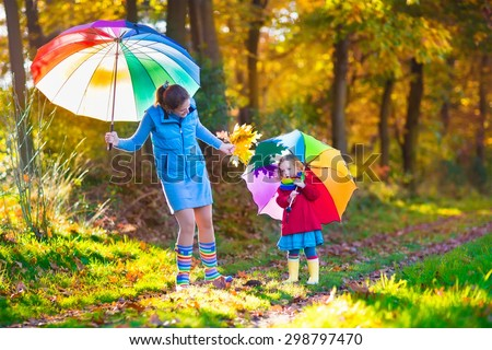 Mother and daughter play in autumn park with golden leaves. Child holding umbrella in the rain. Parent and kid walk in the forest on a rainy fall day. Children playing outdoors with yellow maple leaf - stock photo
