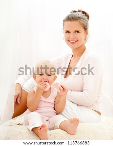 Mother and daughter play in the bedroom