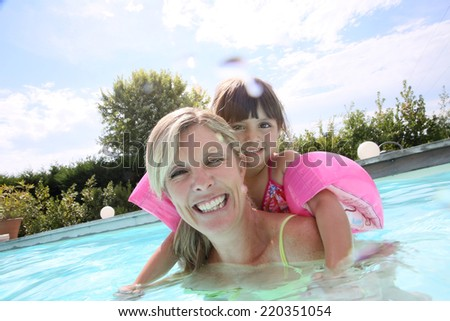 Mother and daughter playing in swimming-pool - stock photo