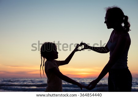 Mother and daughter playing on the beach at the sunset time. Concept of happy friendly family. - stock photo