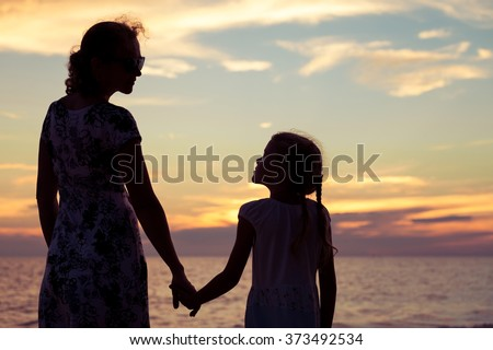 Mother and daughter playing on the beach at the sunset time. Concept of happy friendly family.