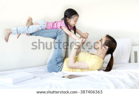 mother and daughter playing on the bed, Asia little girl & mother