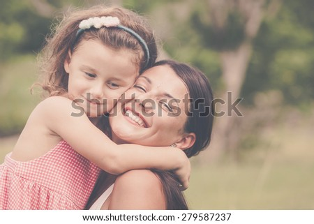 Mother and daughter playing on the grass at the day time. Concept of friendly family.