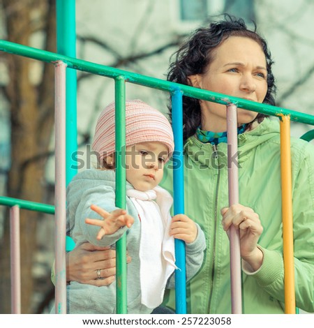 Mother and daughter playing on the playground outdoors on a sunny day - stock photo