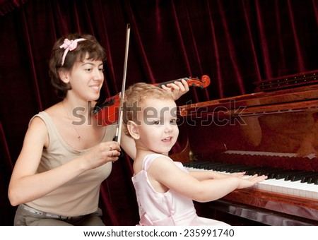 Mother and daughter playing piano and violin. - stock photo