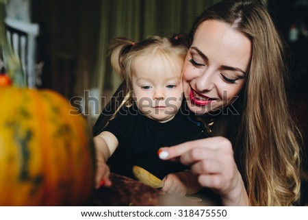 mother and daughter playing together at home on Halloween - stock photo