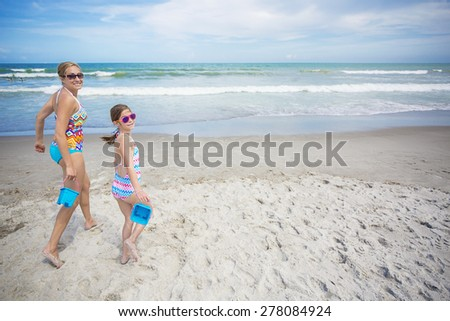 Mother and daughter playing together in the sand on a beautiful beach day. They are running with buckets in hand ready to build something fun together. Lots of copy space - stock photo