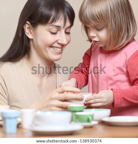 Mother and daughter playing together with little pottery