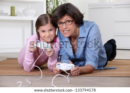 mother and daughter playing video games - stock photo