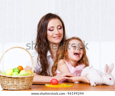 Mother and daughter playing with Easter bunny - stock photo
