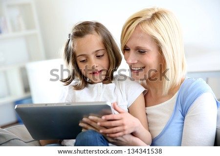 Mother and daughter playing with electronic tablet - stock photo
