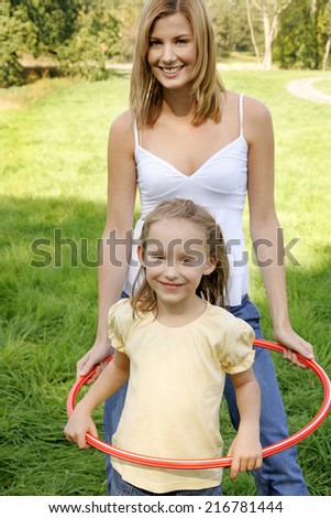 Mother and daughter playing with hula hoops.