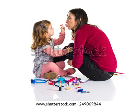 Mother and daughter playing with makeup - stock photo