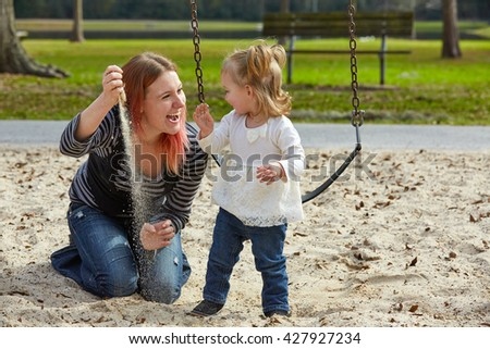Mother and daughter playing with sand having fun at the park playground