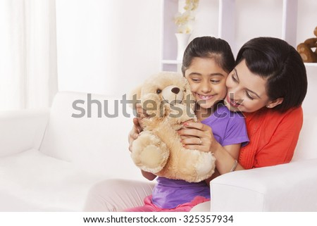 Mother and daughter playing with stuffed toy - stock photo
