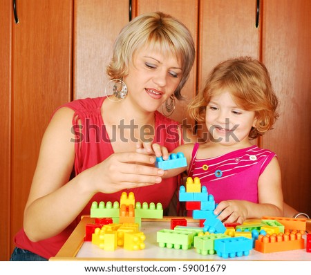 mother and daughter playing with toy blocks