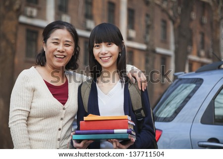 Mother and daughter portrait in front of dormitory - stock photo