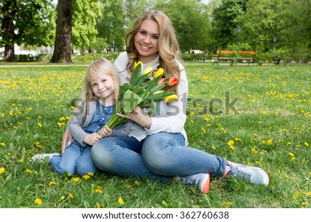 Mother and daughter portrait with flower - stock photo