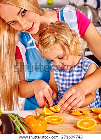 Mother and daughter prepare at kitchen. Interior.
