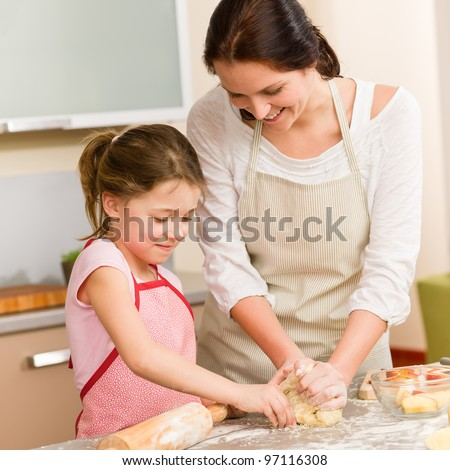Mother and daughter prepare dough baking apple cake happy together - stock photo