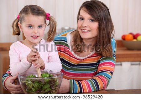 Mother and daughter preparing a salad.