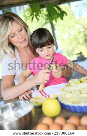 Mother and daughter preparing apple pie - stock photo
