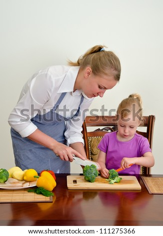 Mother and daughter preparing food. Cutting broccoli with knife.