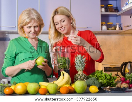 Mother and daughter preparing fruit for making fresh juice