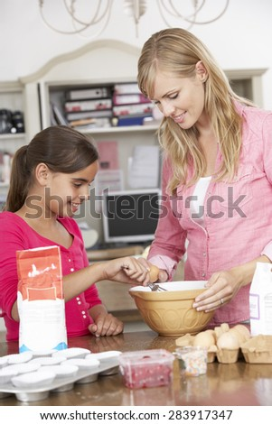 Mother And Daughter Preparing Ingredients To Bake Cakes In Kitchen