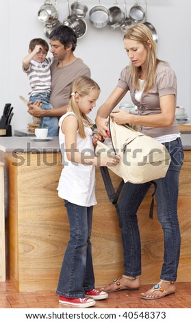 Mother and daughter preparing the bag for school in the kitchen