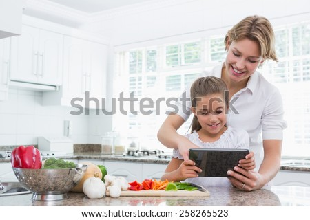 Mother and daughter preparing vegetables at home in kitchen