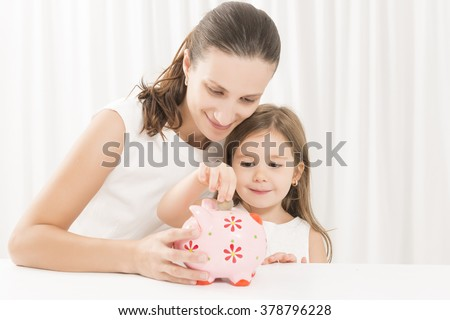 Mother and daughter putting coins into piggy bank. Family budget and savings concept. Junior Savings Account concept - stock photo