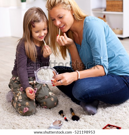 Mother and daughter putting makeup