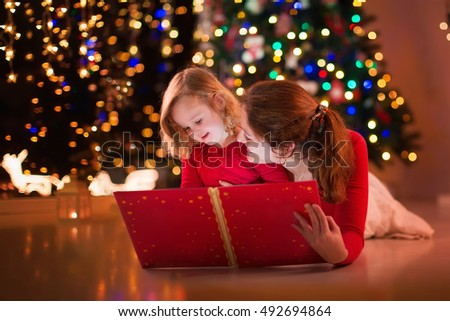 Mother and daughter read a book at fireplace on Christmas eve. Family with child celebrating Xmas. Decorated living room with tree, fire place and candles. Winter evening at home for parents and kids.