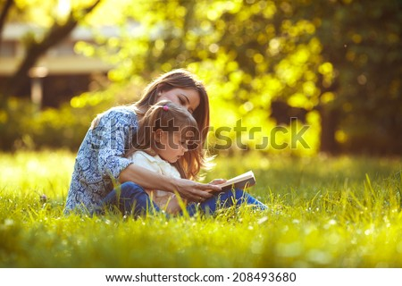 Mother and daughter reading a book at the park. - stock photo