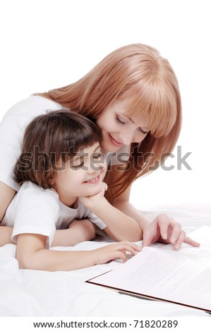Mother and daughter reading a book in a bed studio shot