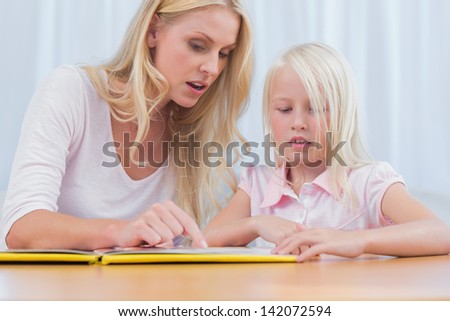 Mother and daughter reading a book together in the living room - stock photo