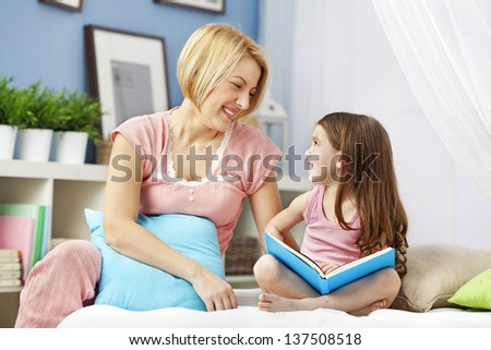 Mother and daughter reading bedtime story , education concept