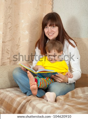 mother and daughter reading book in home