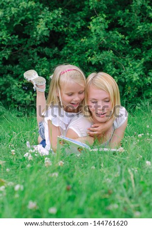 Mother and daughter reading book in the park - stock photo