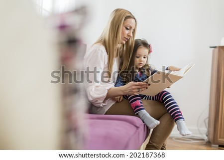 Mother and daughter reading in the room - stock photo