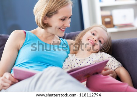 Mother and daughter reading on the couch - stock photo