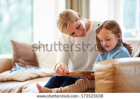 Mother And Daughter Reading Story At Home Together - stock photo