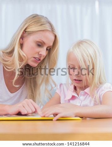 Mother and daughter reading together in the living room - stock photo