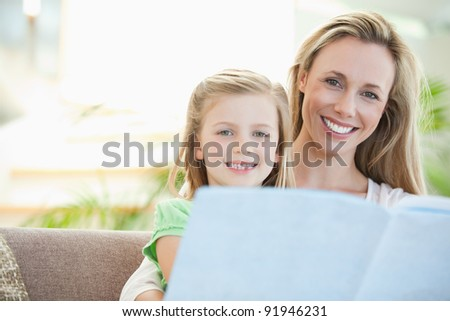 Mother and daughter reading together on the sofa - stock photo