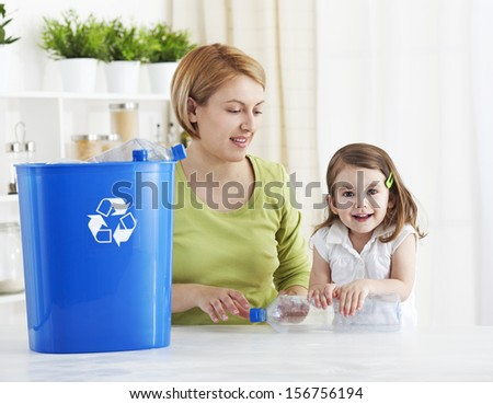 Mother and daughter recycling empty plastic bottle - stock photo