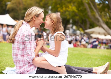 Mother And Daughter Relaxing At Outdoor Summer Event - stock photo